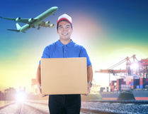 Delivery man holding card box toothy smiling face against shippi Stock Photography