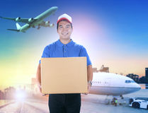 Delivery man holding card box toothy smiling face against shippi Stock Image