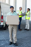 Delivery man is holding a cardboard box and smiling to the camera. Delivery men is holding a cardboard box and smiling to the camera in front of a warehouse Stock Photography
