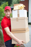 Delivery man holding cardboard boxes Royalty Free Stock Images