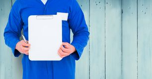Delivery man holding clipboard against wooden background. Mid section of delivery man holding clipboard against wooden background Stock Photos