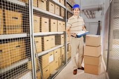 Delivery man holding clipboard by cardboard boxes in warehouse Royalty Free Stock Photos
