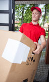 Delivery man holding a heavy box. Young delivery man holding a heavy box Stock Image