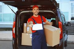 Delivery man holding package clipboard Royalty Free Stock Image