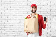 Delivery man holding paper bag with food and phone on brick wall background royalty free stock images