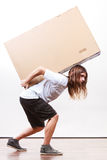 Delivery man holding a paper box. Removal service and delivery concept. Young male guy postal courier holding big very heavy cube package carton Stock Images