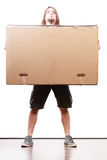 Delivery man holding a paper box. Removal service and delivery concept. Young male guy postal courier holding big very heavy cube package carton Royalty Free Stock Photos