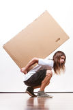 Delivery man holding a paper box. Removal service and delivery concept. Young male guy postal courier holding big very heavy cube package carton Royalty Free Stock Photo