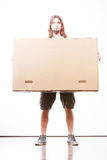 Delivery man holding a paper box. Removal service and delivery concept. Young male guy postal courier holding big very heavy cube package carton Royalty Free Stock Photography