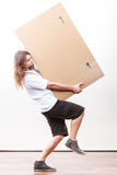 Delivery man holding a paper box. Removal service and delivery concept. Young male guy postal courier holding big very heavy cube package carton Stock Image