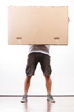 Delivery man holding a paper box. Removal service and delivery concept. Young male guy postal courier holding big very heavy cube package carton Stock Photo