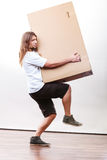 Delivery man holding a paper box. Removal service and delivery concept. Young male guy postal courier holding big very heavy cube package carton Royalty Free Stock Image