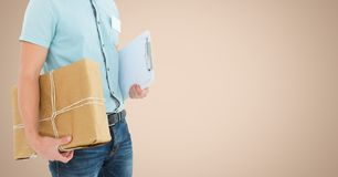 Delivery man holding parcel box and clipboard against beige background Royalty Free Stock Image
