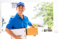 Delivery man holding a parcel box Stock Images