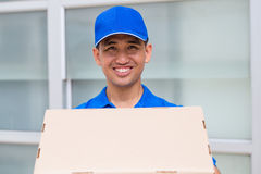 Delivery man holding a parcel box Stock Photos