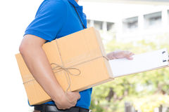 Delivery man holding a parcel box and white paper on clipboard Royalty Free Stock Images