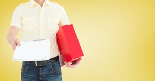 Delivery man holding a parcel and clipboard against yellow background Stock Image