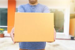 Delivery man holding pile of cardboard boxes in front delivering package to customer, close up at hand and box stock photos