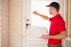 Delivery man holding pizza while knocking on the door Stock Image