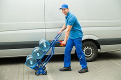 Delivery Man Holding Trolley With Water Bottles Royalty Free Stock Photo