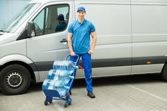 Delivery Man Holding Trolley With Water Bottles Royalty Free Stock Image