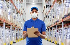 Free Delivery Man In Mask Or Respirator At Warehouse Royalty Free Stock Photo - 178402225