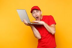 Delivery man isolated on yellow orange background. Professional male employee courier in red cap, t-shirt holding. Working typing on laptop pc computer. Service stock photo