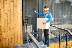 Delivery man with package near the house royalty free stock images