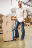 Delivery man leaning on trolley of boxes Royalty Free Stock Photography