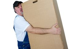 Delivery man lifting heavy cardboard box. Delivery man carrying heavy cardboard box against white background Stock Photography