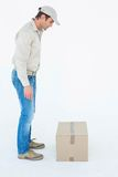 Delivery man looking at cardboard box Stock Photo