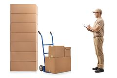 Delivery man looking at a stack of boxes and writing in a clipbo. Full length profile shot of a delivery man looking at a stack of boxes and writing in a Royalty Free Stock Images