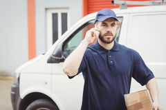 Delivery man making a phone call Royalty Free Stock Photos