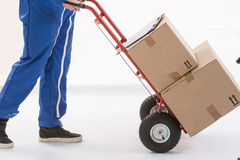 Delivery man moving parcels  with dolly Royalty Free Stock Image