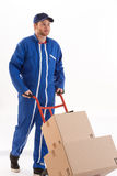 Delivery man moving parcels  with dolly. Delivery man moving boxes with dolly, isolated on white background Royalty Free Stock Photo