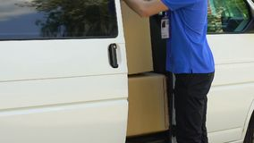 Delivery man opening door of company car and taking parcel, express delivery. Stock footage stock footage