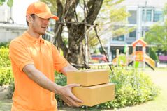 Delivery man in orange is handing customer the package. Delivery man in orange shirt is handing customer the package Stock Images