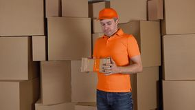 Delivery man in orange uniform delivering damaged parcel to customer. Brown cartons background. Flaw and unprofessional