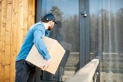 Delivery man with package near the house royalty free stock photo
