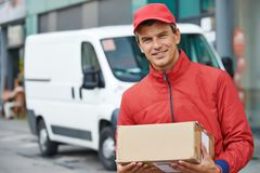 Delivery man with package outdoors Royalty Free Stock Photos