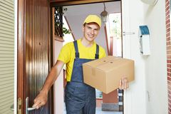 Delivery man with parcel box indoors Royalty Free Stock Image
