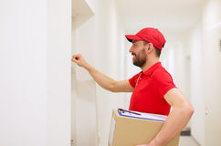 Delivery man with parcel box knocking on door Royalty Free Stock Images