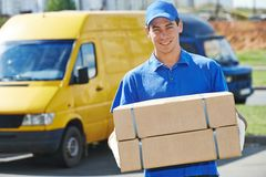 Delivery man with parcel box. Smiling young male postal delivery courier man in front of cargo van delivering package