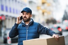 Delivery man with a parcel box on the street. Delivery man holding a parcel box on the street - courier service concept. A man with a smartphone making a phone royalty free stock photos