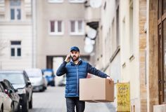 Delivery man with a parcel box on the street. Delivery man holding a parcel box on the street - courier service concept. A man with a smartphone making a phone Royalty Free Stock Image