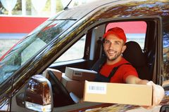 Delivery man with parcel. In car stock photos