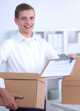 Delivery man with  parcel and a tablet standing in Royalty Free Stock Images