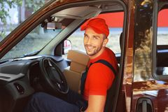 Delivery man with parcels. In car Stock Images