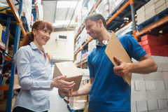 Delivery man passing parcel to warehouse manager Stock Images