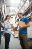 Delivery man passing parcel to warehouse manager Royalty Free Stock Photos